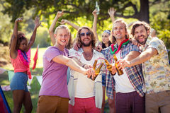 Happy friends toasting beer bottles at campsite. Portrait of happy friends toasting beer bottles at campsite on a sunny day Royalty Free Stock Photos