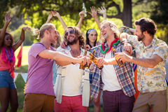 Happy friends toasting beer bottles at campsite. On a sunny day Stock Photos