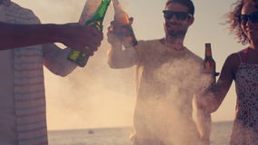 Happy friends toasting beers on the beach. In slow motion stock video