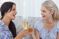 Happy friends toasting with champagne. At home on the couch Stock Images