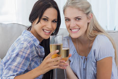 Happy friends toasting with champagne and looking at camera. At home on the couch Royalty Free Stock Photo