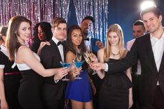 Happy friends toasting drinks at nightclub Stock Image