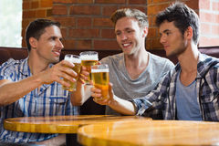 Happy friends toasting with pints of beer Stock Photo