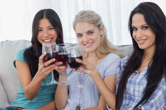 Happy friends toasting with red wine together and looking at cam. Era at home on couch Stock Photo