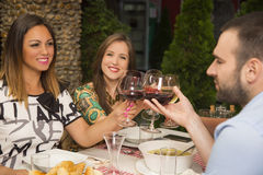 Happy friends toasting with wine at a restaurant. Royalty Free Stock Image