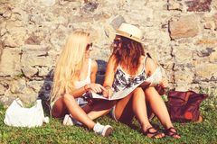 Happy friends travel together in summertime. Joyful women expressing positivity. Traveler girls using map outdoors. Summer. Vacation. Travel holiday relaxation stock photography