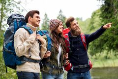 Happy friends or travelers with backpacks hiking stock photo