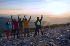 Happy friends, travelers, with open arms in the mountains stock images
