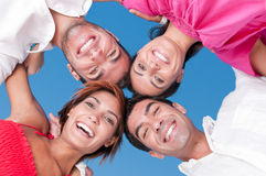 Happy friends united. Happy smiling friends with their heads together looking at camera in a sunny day Stock Image