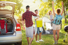 Happy friends unpacking car for camping trip. Group of happy friends unpacking car for camping trip royalty free stock image