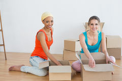 Happy friends unwrapping boxes in a new house Royalty Free Stock Photo