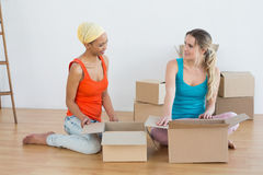 Happy friends unwrapping boxes in a new house Stock Photo
