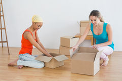 Happy friends unwrapping boxes in a new house Stock Image