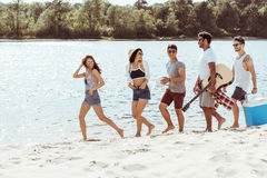 Happy friends walking on beach on summer day royalty free stock photo