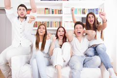 Happy friends watching football match on tv. Cheering Royalty Free Stock Photography