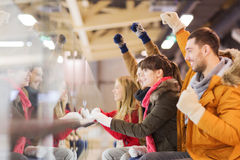 Happy friends watching hockey game on skating rink Royalty Free Stock Image