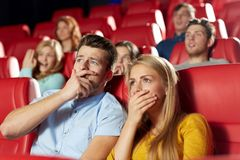 Happy friends watching horror movie in theater. Cinema, entertainment and people concept - happy friends watching horror, drama or thriller movie in theater Stock Images