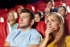 Happy friends watching horror movie in theater. Cinema, entertainment and people concept - happy friends watching horror, drama or thriller movie in theater Stock Photography