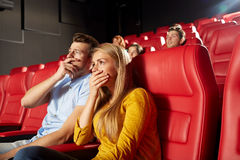 Happy friends watching horror movie in theater. Cinema, entertainment and people concept - happy friends watching horror, drama or thriller movie in theater Royalty Free Stock Photography
