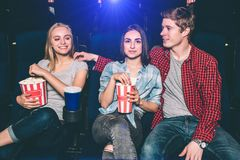 Happy friends are watching movie. They are sitting together. Guy is looking at blonde girl. She is happy about that. Brunette girl is looking forward and stock image