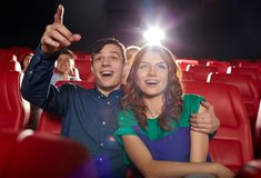 Happy friends watching movie in theater. Cinema, entertainment, gesture, emotions and people concept - happy friends watching movie pointing finger to screen in royalty free stock images