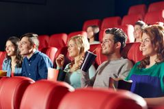 Happy friends watching movie in theater Royalty Free Stock Image