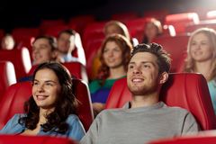 Happy friends watching movie in theater. Cinema, entertainment and people concept - happy friends watching movie in theater royalty free stock images