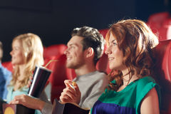 Happy friends watching movie in theater. Cinema, entertainment and people concept - happy friends watching movie in theater stock images