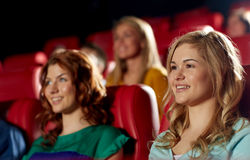 Happy friends watching movie in theater. Cinema, entertainment and people concept - happy friends watching movie in theater royalty free stock photo
