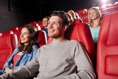 Happy friends watching movie in theater. Cinema, entertainment and people concept - happy friends watching movie in theater stock photography