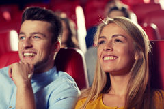 Happy friends watching movie in theater. Cinema, entertainment and people concept - happy friends watching movie in theater royalty free stock photos