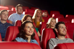 Happy friends watching movie in theater. Cinema, entertainment and people concept - happy friends watching movie in theater royalty free stock photography