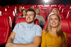 Happy friends watching movie in theater. Cinema, entertainment and people concept - happy friends watching movie in theater stock photo