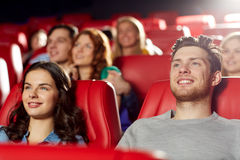 Happy friends watching movie in theater. Cinema, entertainment and people concept - happy friends watching movie in theater royalty free stock image
