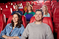 Happy friends watching movie in theater. Cinema, entertainment and people concept - happy friends watching movie in theater stock image