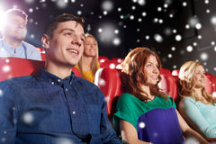 Happy friends watching movie in theater. Cinema, entertainment and people concept - happy friends watching movie in theater over snowflakes stock image