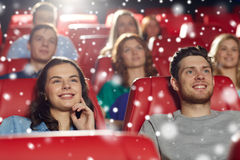 Happy friends watching movie in theater. Cinema, entertainment and people concept - happy friends watching movie in theater with snowflakes royalty free stock photos