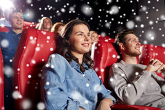 Happy friends watching movie in theater. Cinema, entertainment and people concept - happy friends watching movie in theater with snowflakes stock photos