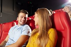 Happy friends watching movie in theater. Cinema, entertainment and people concept - happy friends watching movie and talking in theater stock images