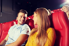 Happy friends watching movie in theater. Cinema, entertainment and people concept - happy friends watching movie and talking in theater stock photography
