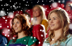 Happy friends watching movie in theater. Cinema, entertainment and people concept - happy women with friends watching movie in theater over snowflakes royalty free stock images