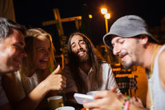 Happy friends watching photos on the cell. Group of happy friends having joyful evening in outdoor cafe and watching photos on smart phone royalty free stock images