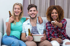 Happy friends watching soccer match while sitting on sofa Stock Photo
