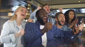 Happy friends watching sports in bar, rejoicing winning game, leisure activity. Stock footage stock video