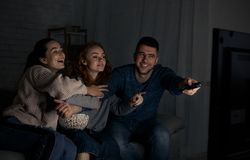 Happy friends watching TV and switching channels. Don`t switch. Happy friends watching TV and switching channels at home royalty free stock image