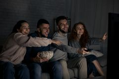 Happy friends watching TV and switching channels. At home stock image