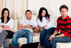 Happy friends watching tv together. Happy friends sitting comfortable on couch and watching tv Royalty Free Stock Photo