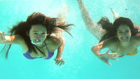 Happy friends waving at camera underwater. In slow motion stock video footage