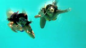 Happy friends waving at camera underwater wearing snorkels. In slow motion stock video footage