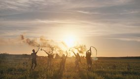 Happy friends waving colorful smoke at sunset. Happy friends waving colorful smoke at sunset stock footage